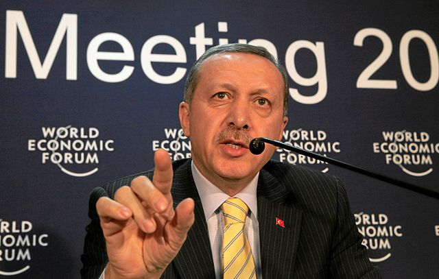 Turkey's 2009 Prime Minister, Recep Tayyip Erdoğan, raising his finger as he speaks at the microphone at the World Economic Forum in Davos. He is a light brown-skinned man with greying hair and a moustache and wears a grey pinstriped suit, white shirt, yellow tie and red pin. He is in front of a dark blue backdrop with 'Meeting 20...' and 'World Economic Forum' (repeated) in white lettering.