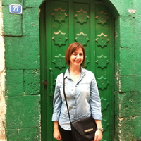 Selin Akyuz, a red-haired woman with a light blue shirt and black shoulder bag, stands in front of a green door and green wall.